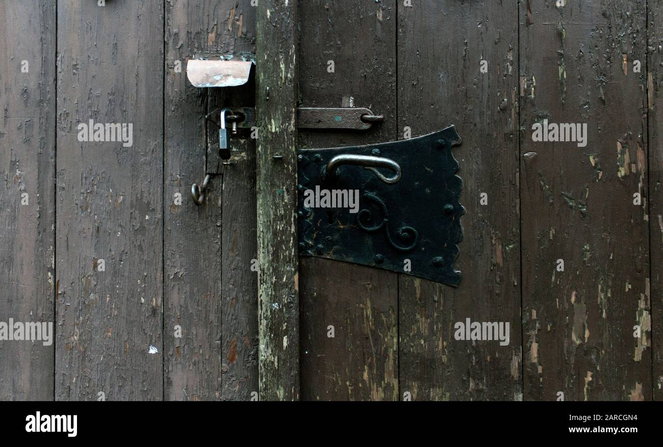 Close up of old and new iron locks on wooden door. Technological change, security concepts. Stock Photo