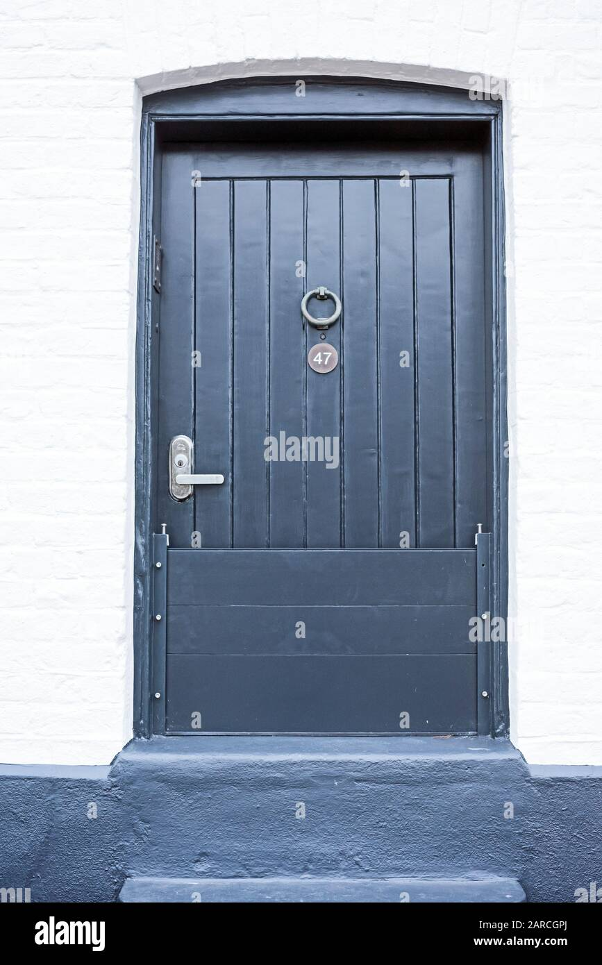 Unusual three quarter sized front door to riverside house with raised step, as part of flood defences, at Strand on the Green, Kew, London, UK. Stock Photo