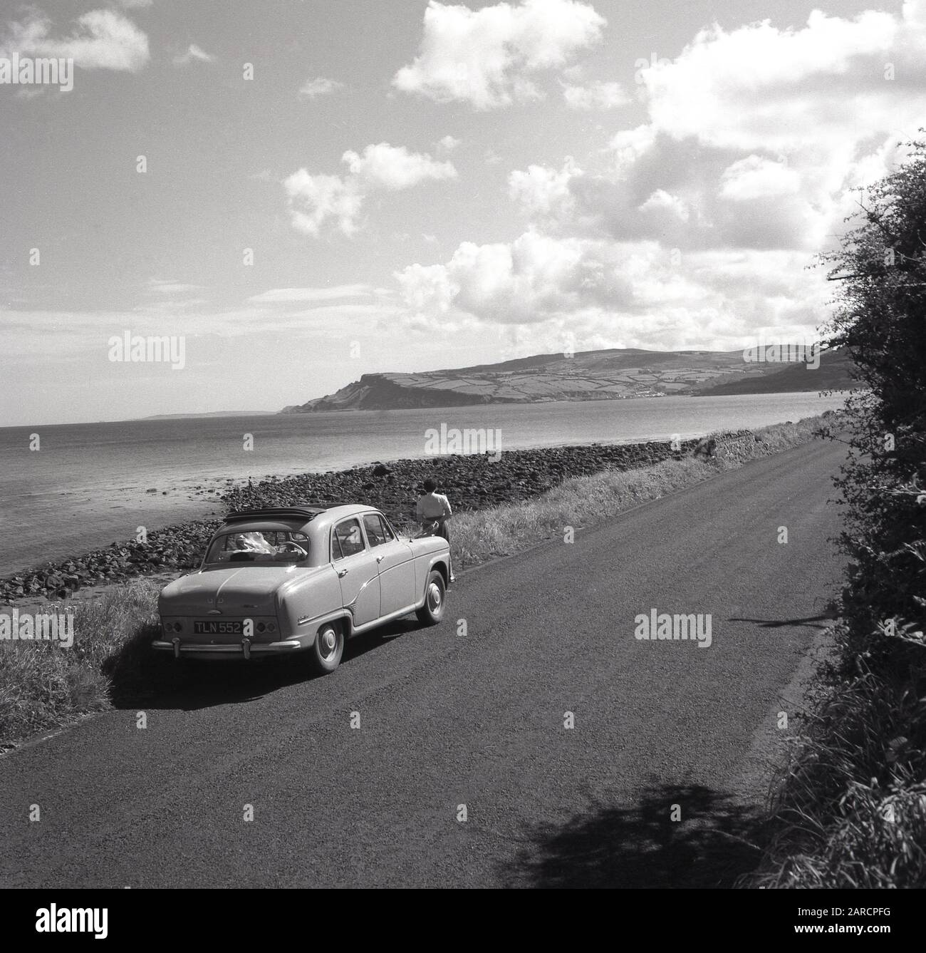 1950s, historical, a lady traveller standing by her motor car of the era on a quiet road looking over a bay on the Causeway coastal route, with the Antrim mountains in the distance, Co. Antirm, Northern Ireland, UK. The driving route, known as one of the greatest drives on earth, is famed for its spectacular setting overlooking the Antrim coast. Stock Photo