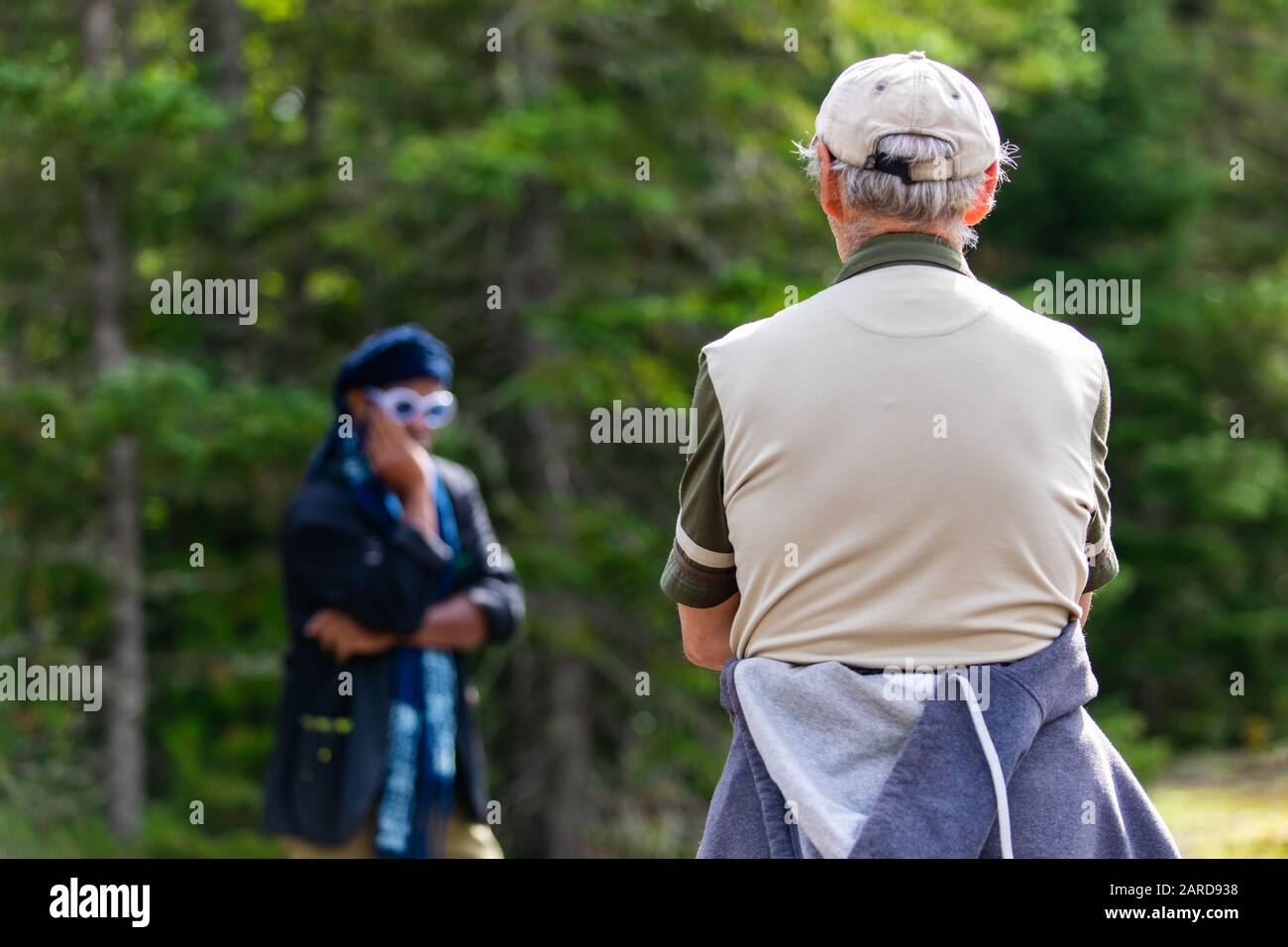 Closeup rear view of man looking at fashionable stylish man wearing sunglasses and scarf while standing against trees in forest during vacation Stock Photo