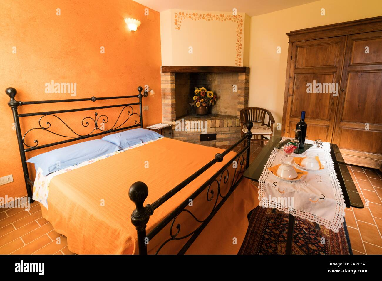 San Quirico Italy Typical Interior Of A Agriturismo In Tuscany With Stone Fireplace And Wrought Iron Bed In A Room Painted In Sunset Orange Stock Photo Alamy