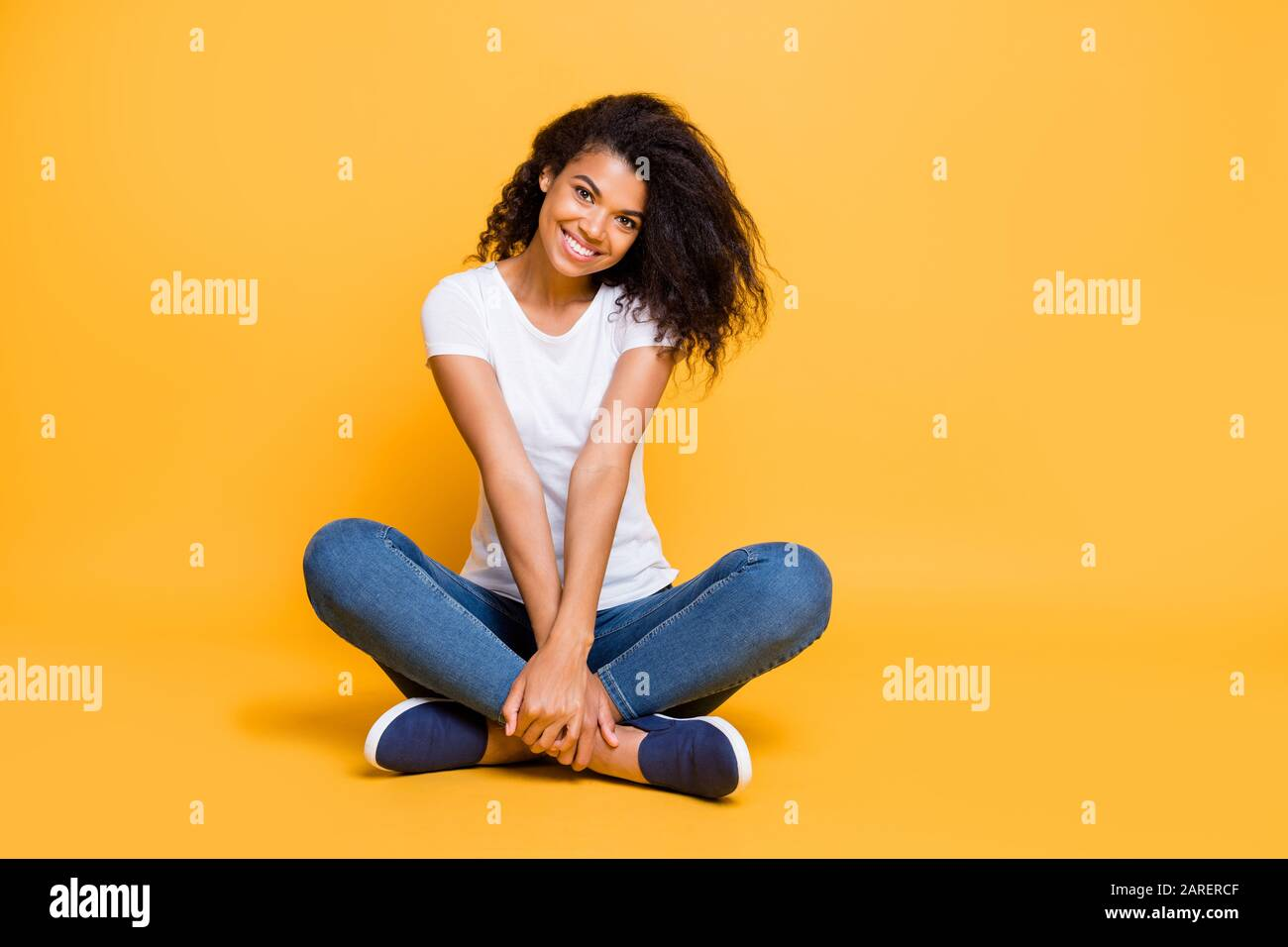 Full length body size photo of cheerful positive cute nice charming pretty girl in jeans denim footwear sitting with legs crossed isolated over vivid Stock Photo