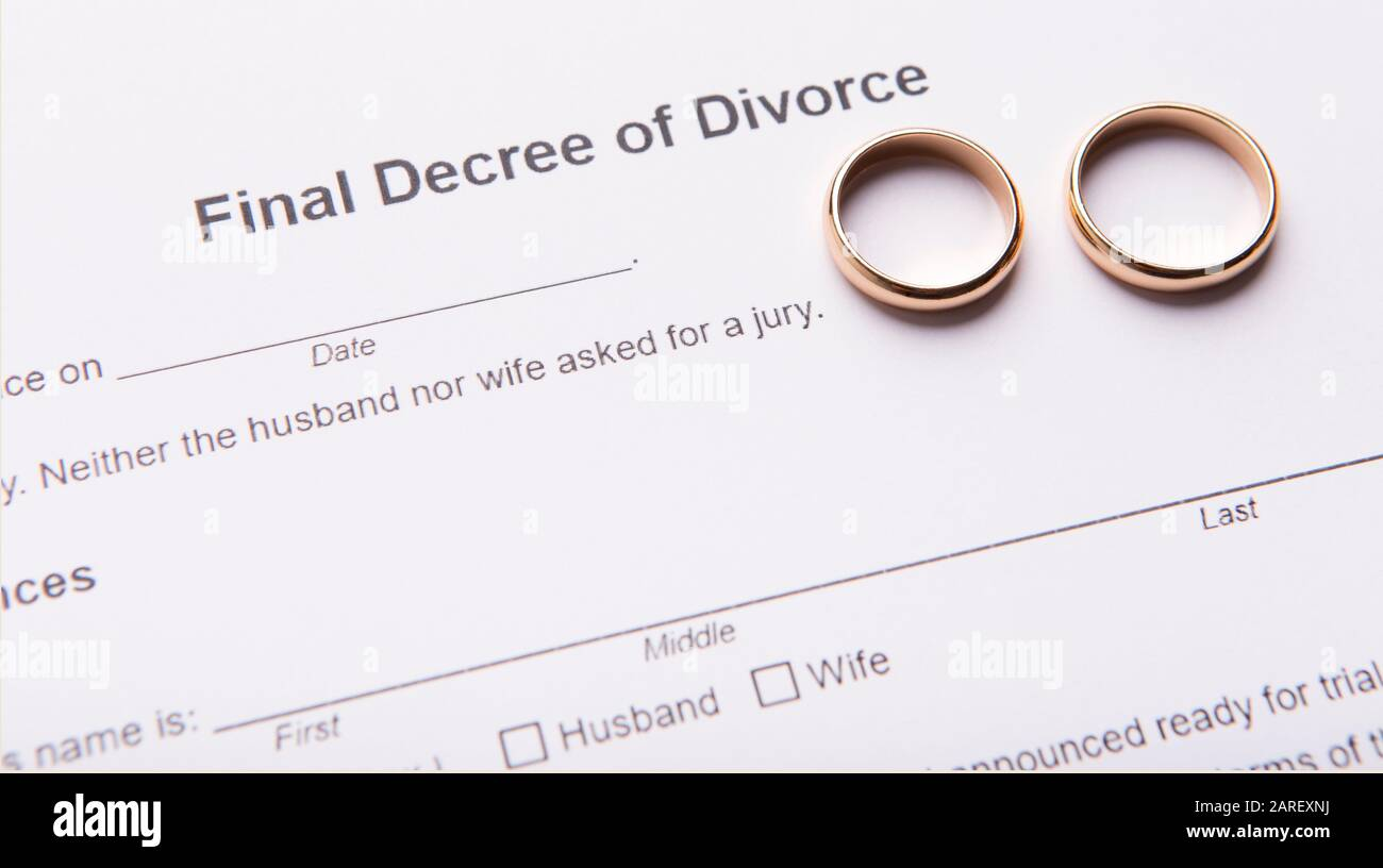 Two golden wedding rings on final divorce decree document Stock Photo