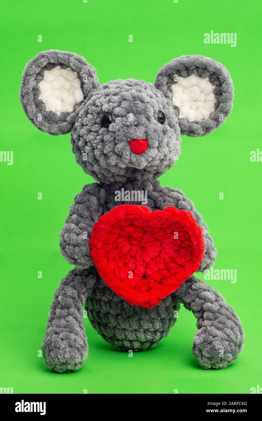 Grey knitted mouse with a heart in hand on a green background. Stock Photo