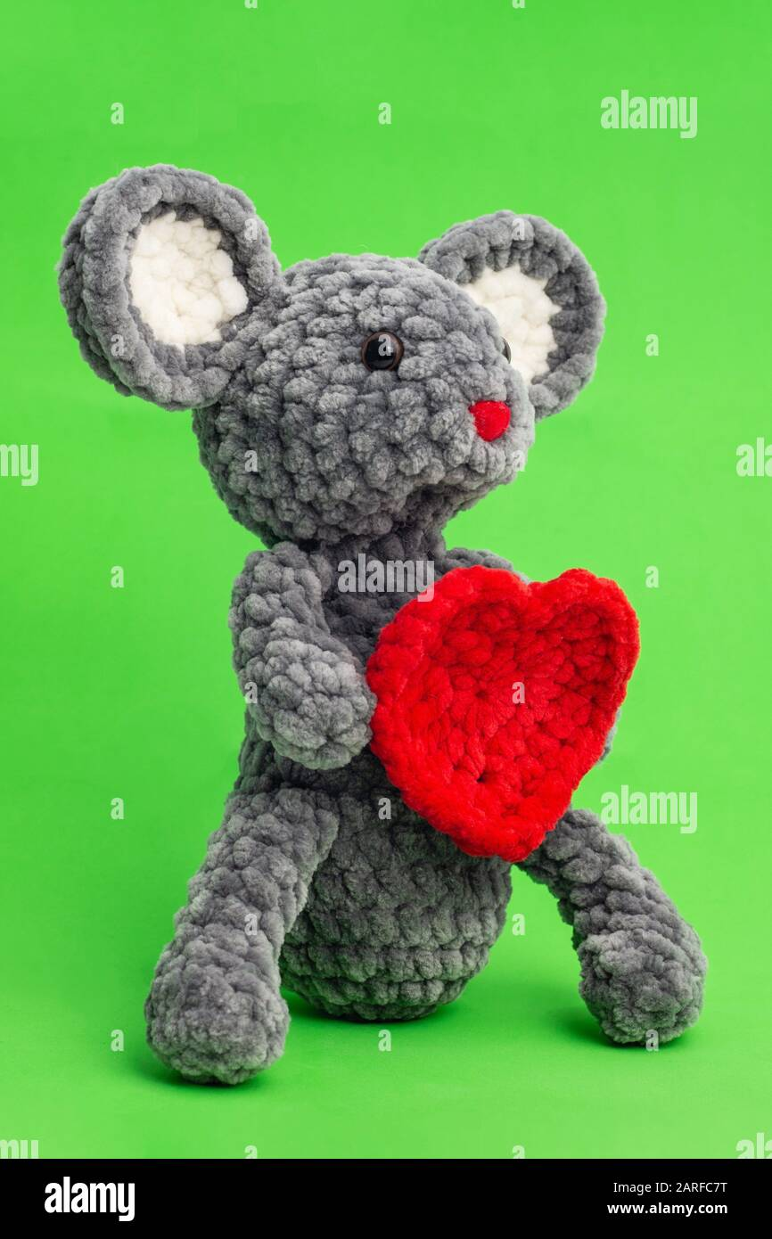 Grey knitted mouse with a heart in hand on a green background, side view. Stock Photo