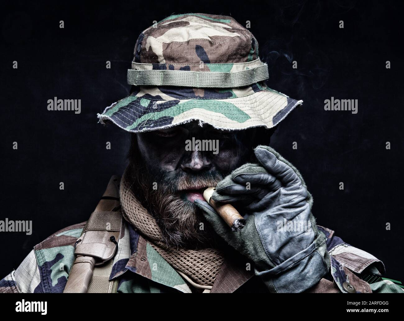 Brutal and serious commando soldier, army special forces veteran, in camouflage battle uniform, boonie hat, black paint on bearded face, combat knife Stock Photo