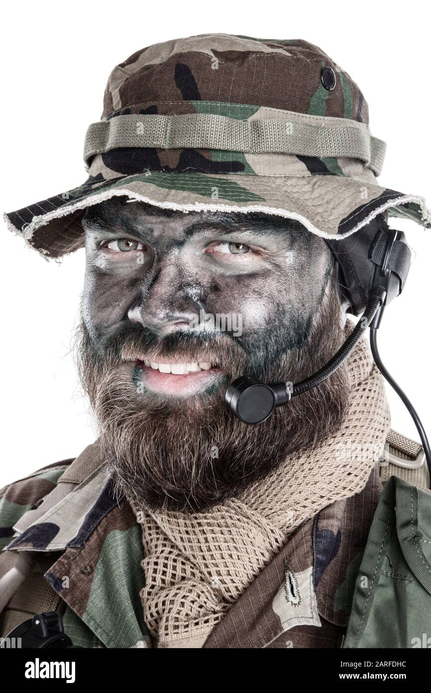 Shoulder studio portrait of commando soldier, modern mercenary, professional soldier with black camouflage paint on bearded face, tactical radio Stock Photo