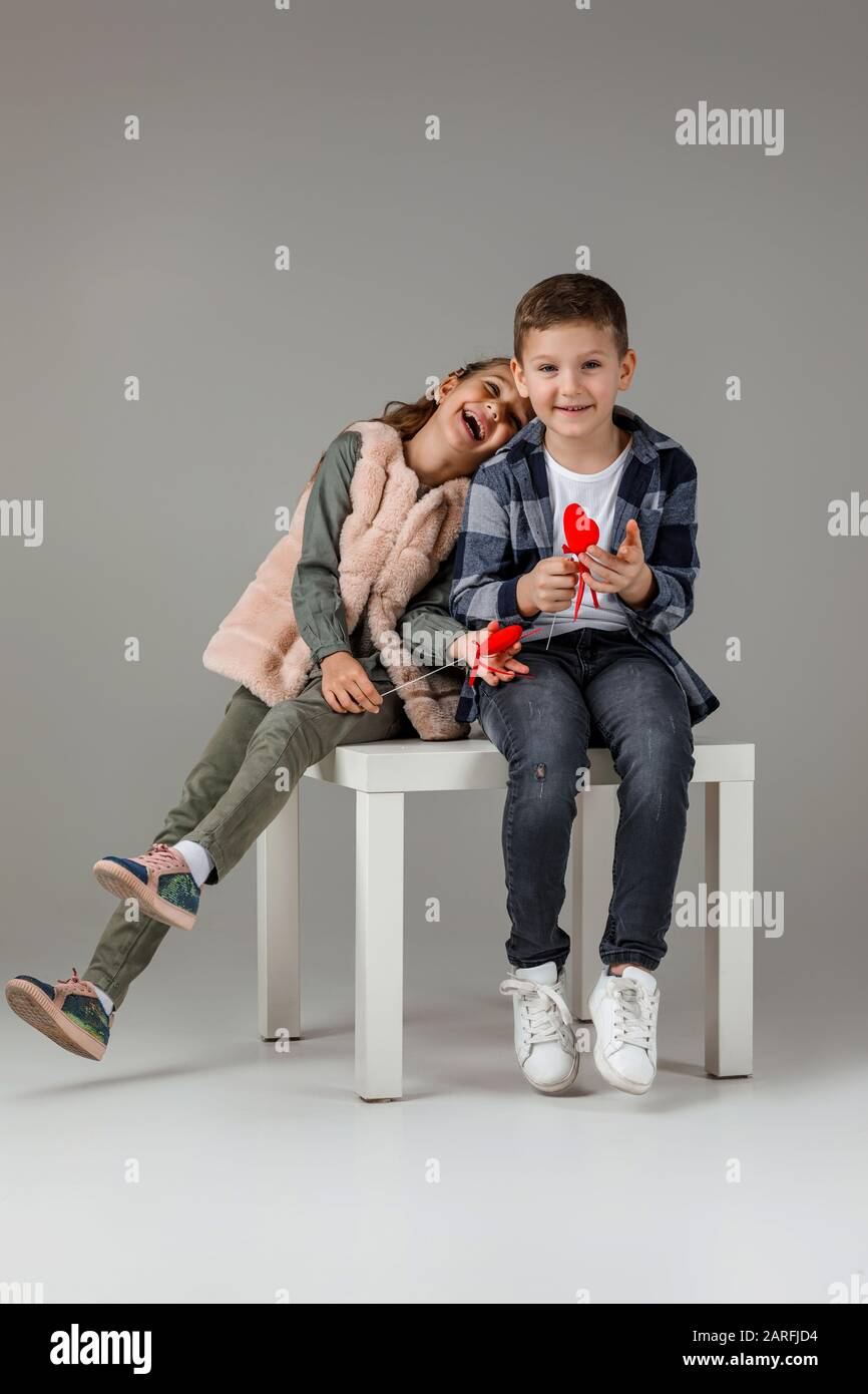 Cute stylish little couple child girl and boy with red hearts on stick in fashionable clothes sittting together at studio. kids fashion concept. St. Valentine's Day. Stock Photo