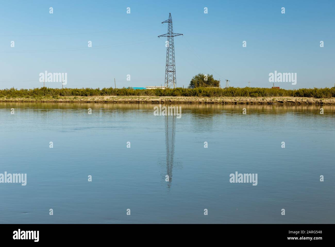 power line pylon stands on the banks of the Syr Darya river, reflected in the water, Kazakhstan. Power line crosses the river Stock Photo