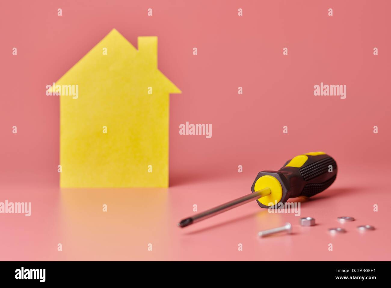 House renovation concept. Home repair and redecorated. Screws and yellow house shaped figure on pink background. Stock Photo
