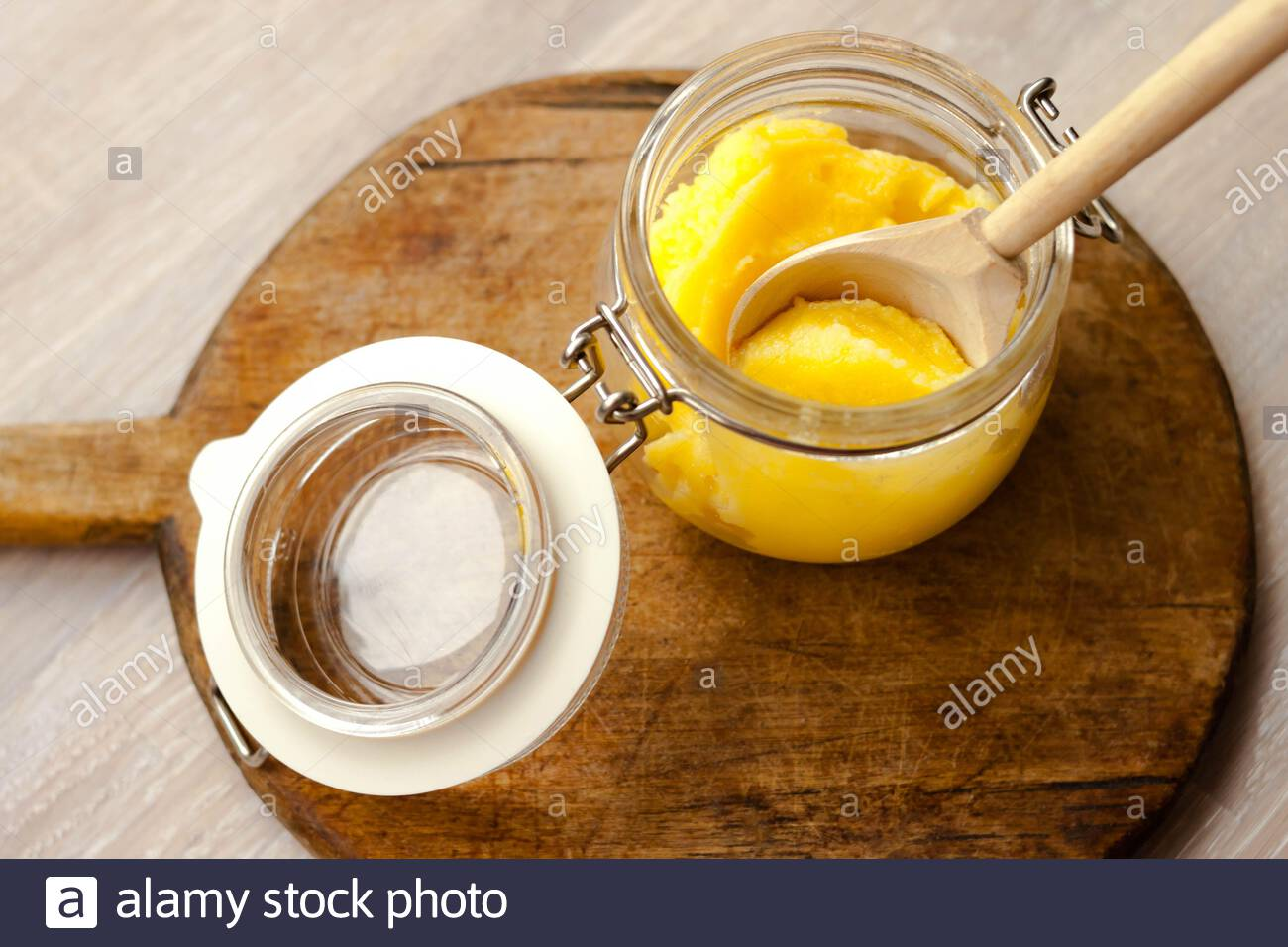 Ghee clarified butter desi in glass jar with spoon made from wood on natural wooden background Stock Photo