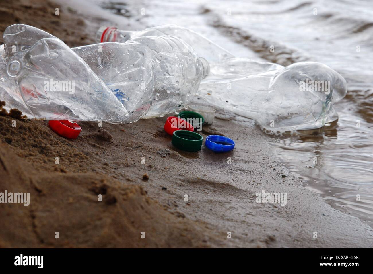 Plastic waste left by campers at river or lake shore, bottles and plastic bottle caps on the sand in the water close up Stock Photo