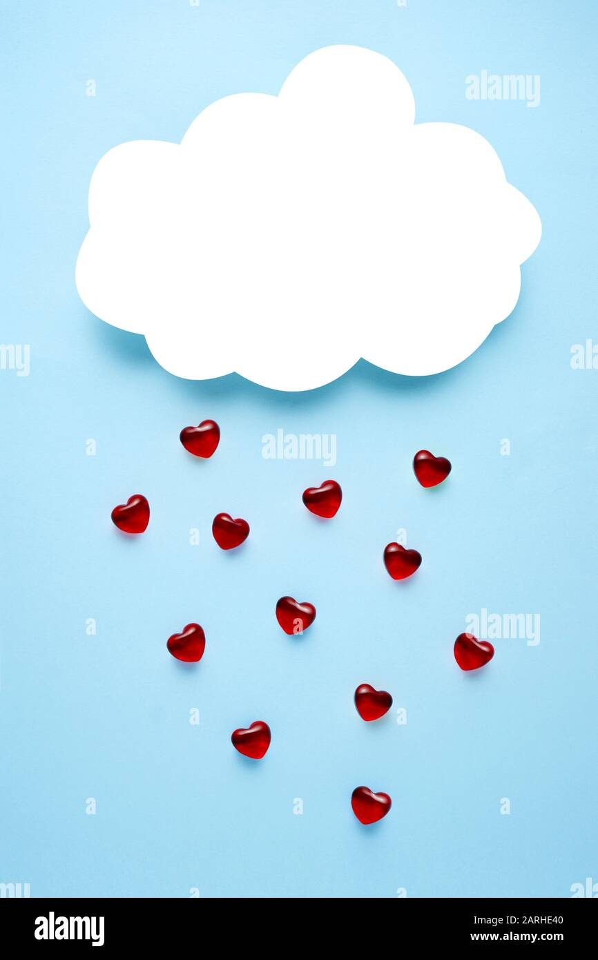 Creative concept holiday valentines day love photo of handmade paper cloud raining with hearts on blue background. Stock Photo