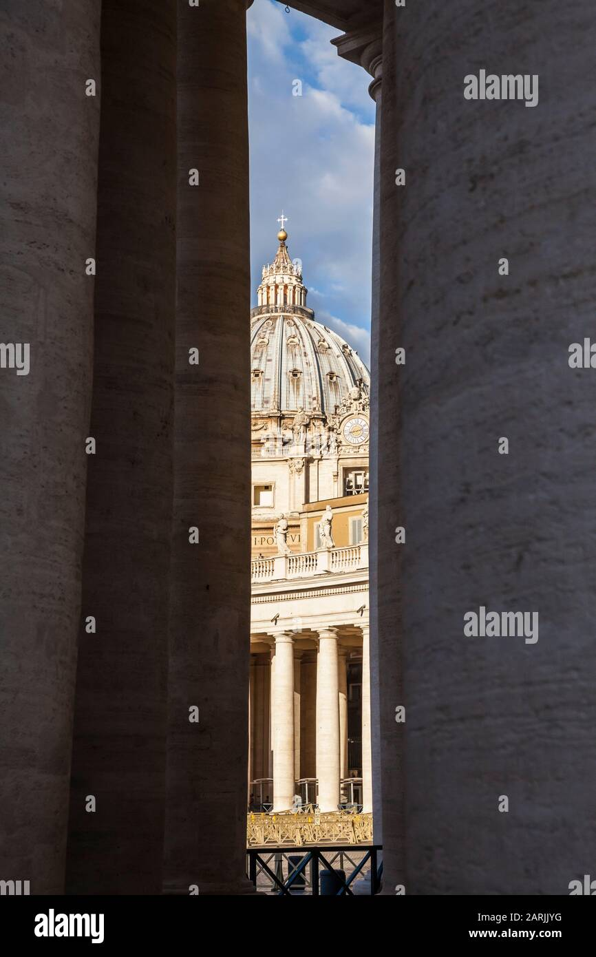 A view of St. Peters Basilica between the pillars of the colonnade around St. Peters Square, Vatican City. Stock Photo