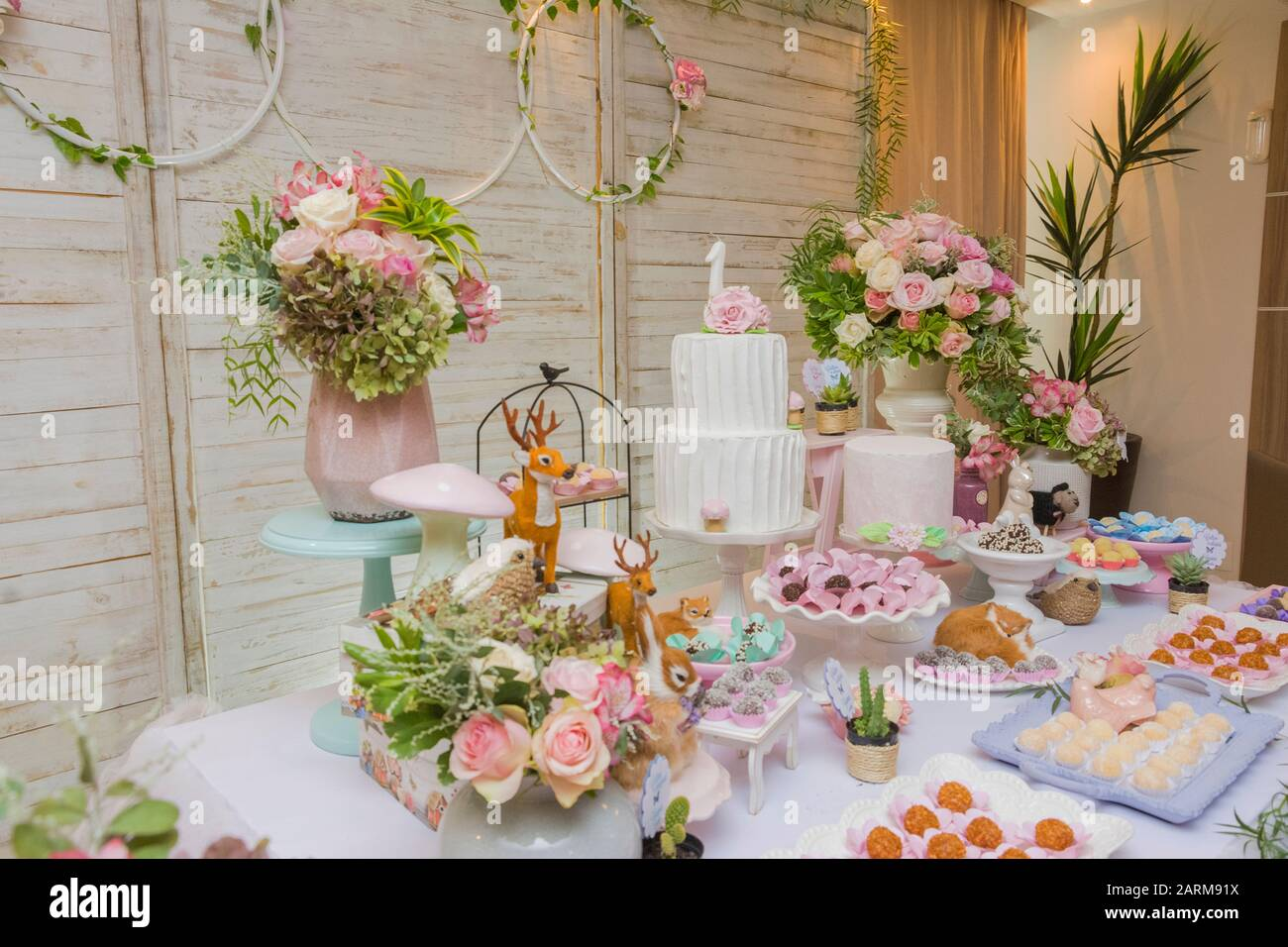 Details Of Luxurious Table Of Sweets And Birthday Cake Decorated With Flower Arrangements And Delicate Wild Animals With Light Wood Panel In The Backg Stock Photo Alamy