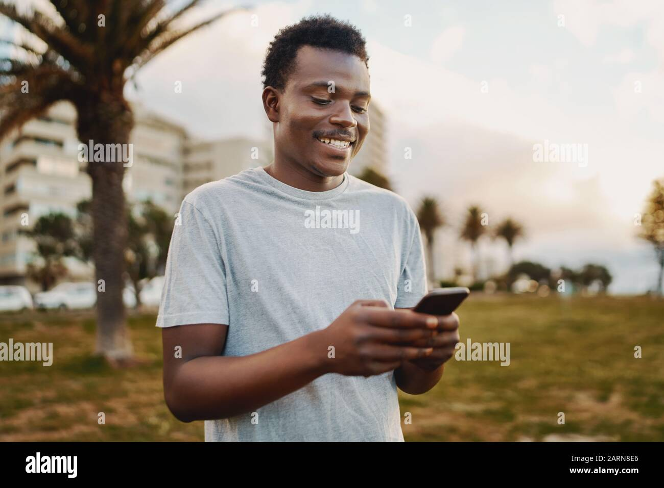 Portrait of a sportive young african american man smiling while texting messages on mobile phone in the park Stock Photo