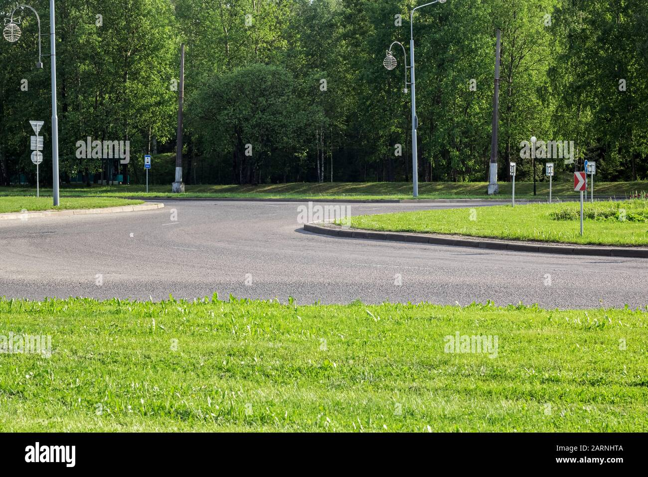 Road for transport with road signs among green grass Stock Photo