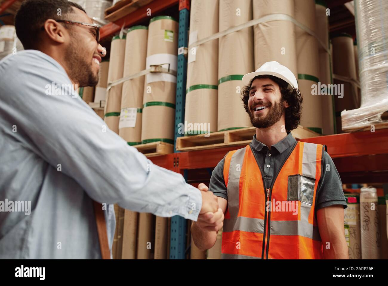 Young partners congratulating each other on new business deal while standing in a modern factory Stock Photo
