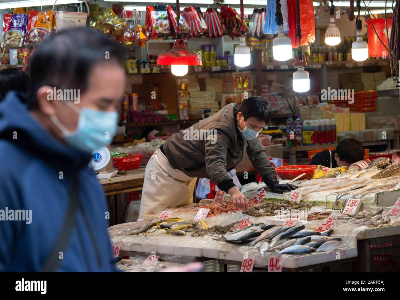 Hong Kong, China. 29th Jan, 2020. Fear of the 2019 Novel Coronavirus from Wuhan China is evident on the streets of Hong Kong. A North point market fishmonger a surgical mask. Credit: Jayne Russell/Alamy Live News Stock Photo