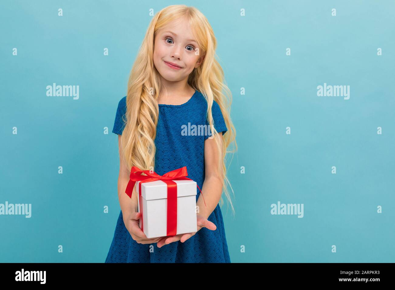 Cute Blond Child In A Dress With A Gift In His Hands On A Light