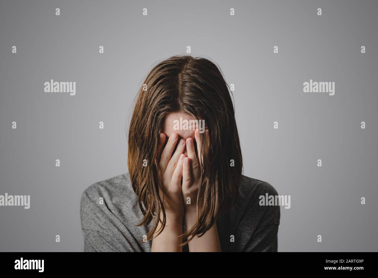 Woman covers face in hands. Concept of despair, depression, loss or mental condition Stock Photo