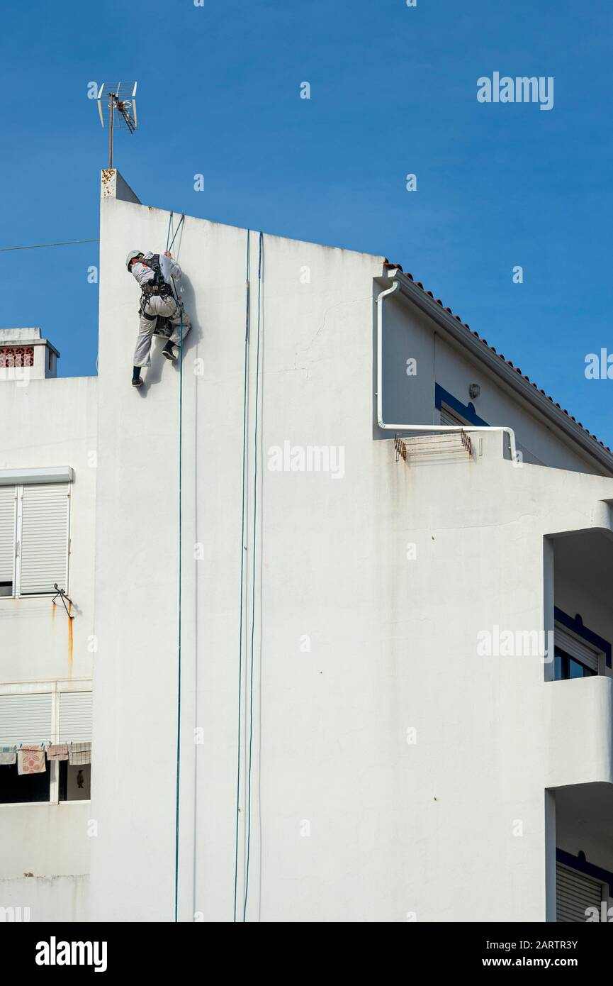 Rope access abseiler, building repairs and painter wearing full safety body harness on the side of a building Stock Photo