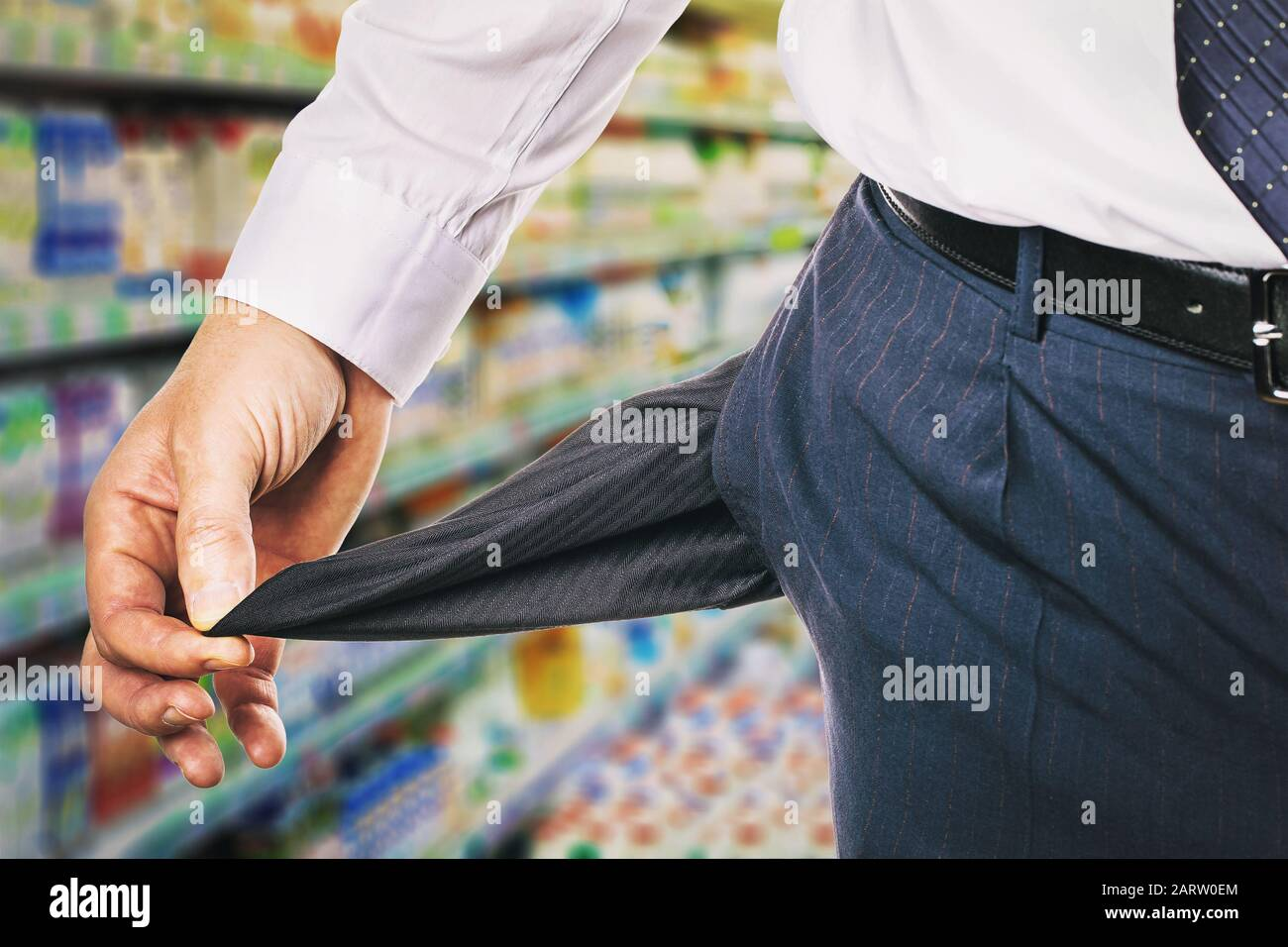 Man shows an empty pocket on the background of the store. The concept of the lack of money for purchases Stock Photo