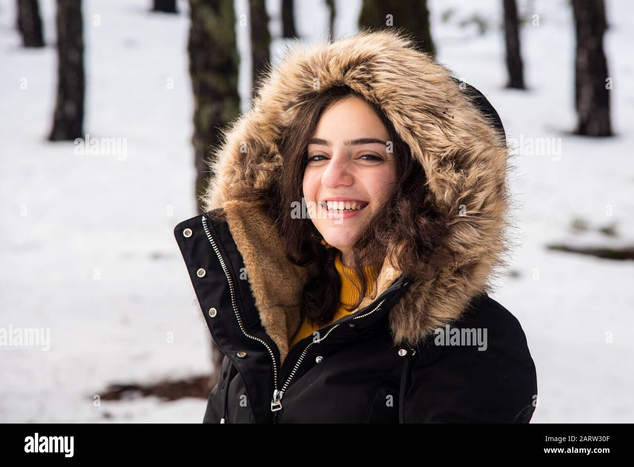 Portrait of a Young happy and beautiful teenage girl dressed in winter clothing standing at snow and smiling. Troodos mountains in Cyprus Stock Photo