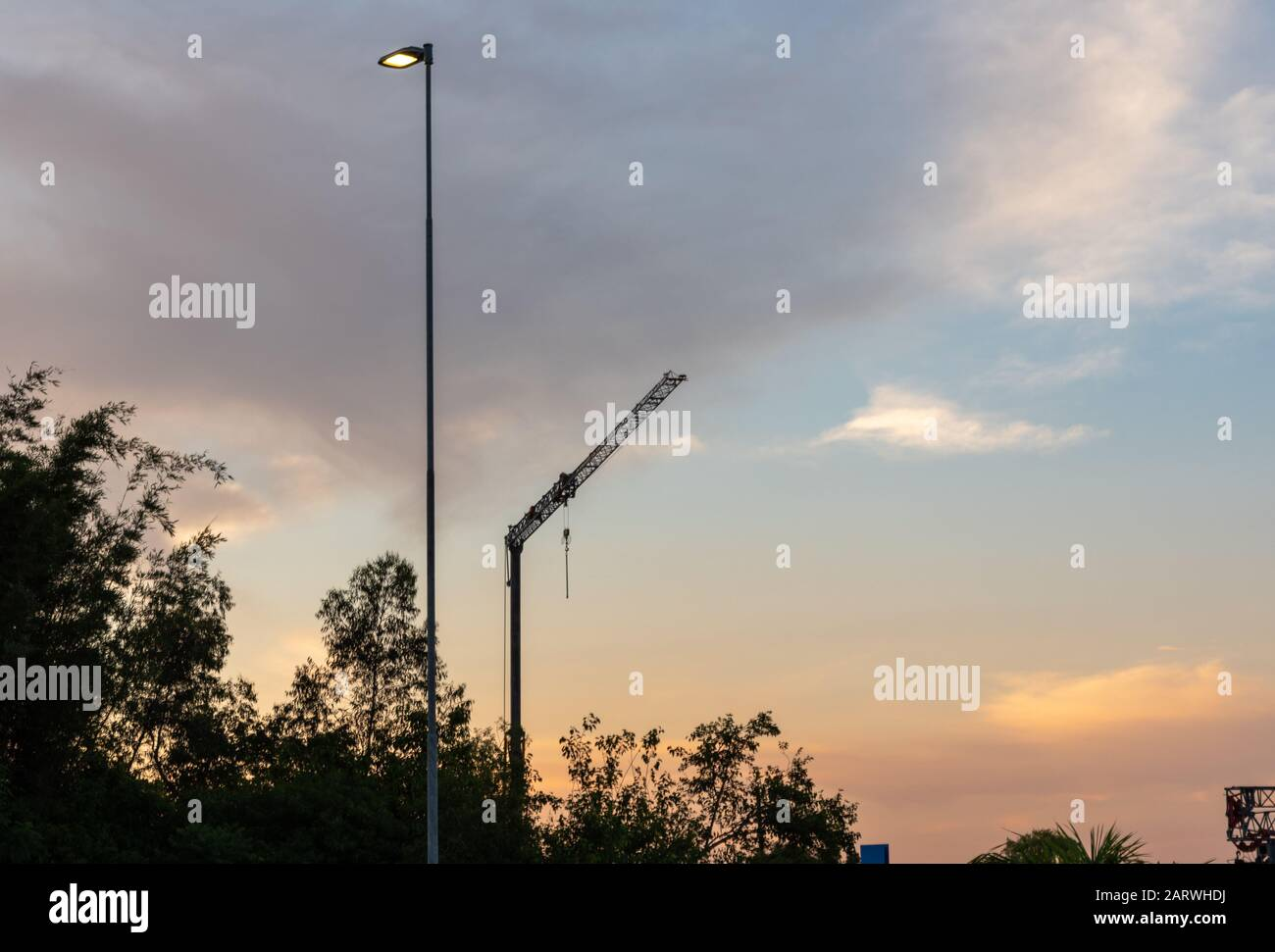 A power pole with light on cesa and the silhouette of a construction crane. Energy and architecture and engineering equipment. Stock Photo