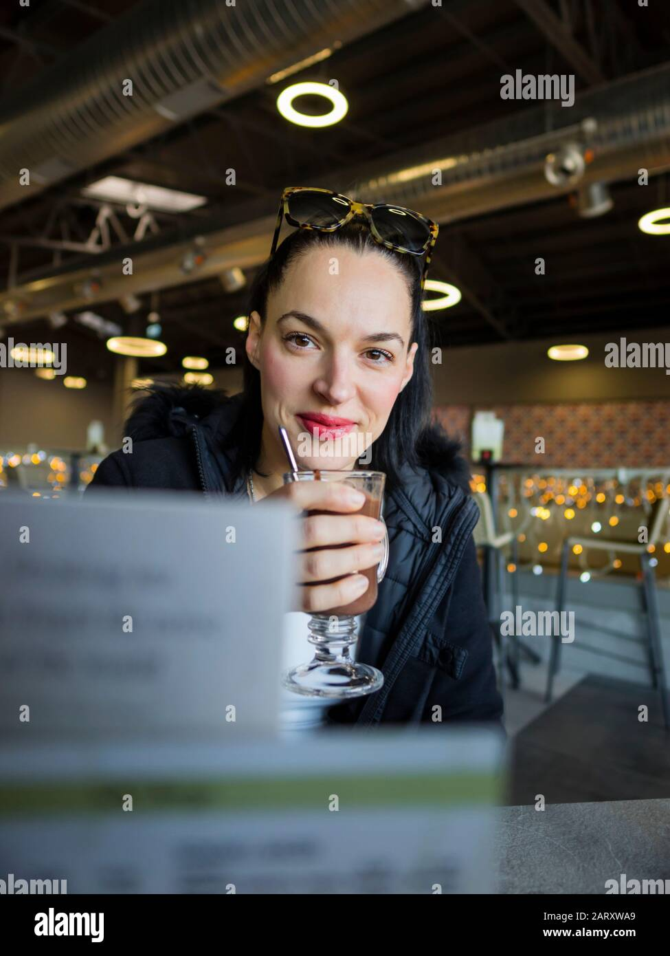 Drinking hot chocolate beverage smiling looking at camera sitting in bar behind price list Stock Photo