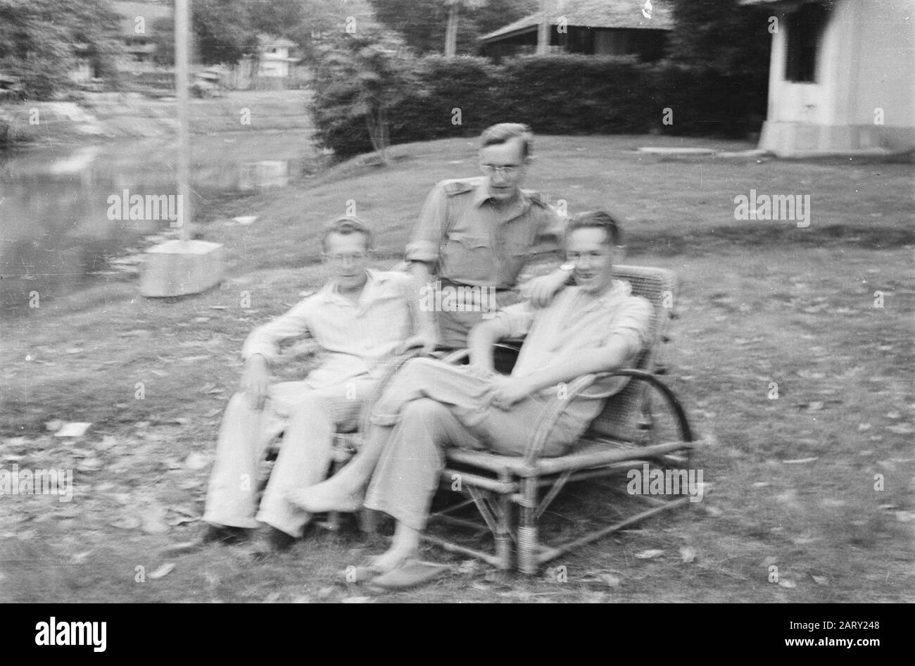Two Men In Pajamas Sitting In Wicker Chairs Between Them An Administrative Officer Location On A