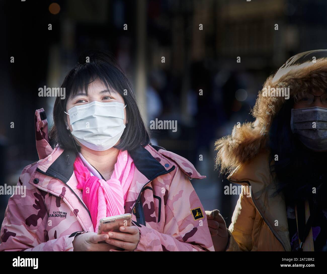 Face mask worn by a chinese tourist outside the railway station in Cambridge, England, on 30 january 2020, to prevent catching the coronavirus flu. Stock Photo
