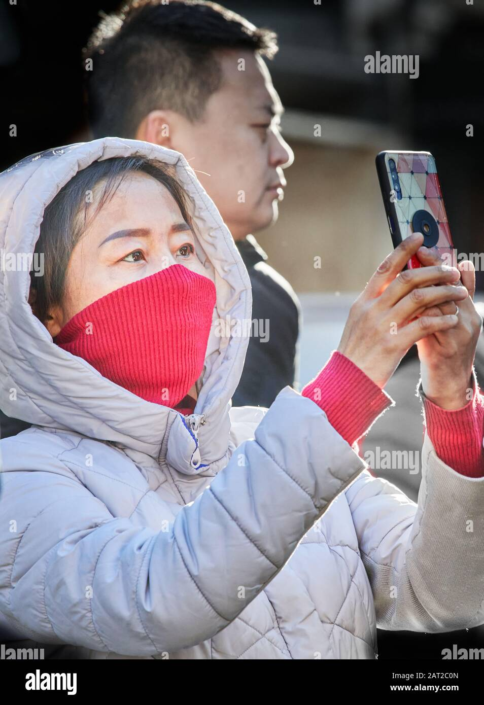 Face mask worn by a chinese tourist outside Trinity college, Cambridge, England, on 30 january 2020, to prevent catching the coronavirus flu. Stock Photo