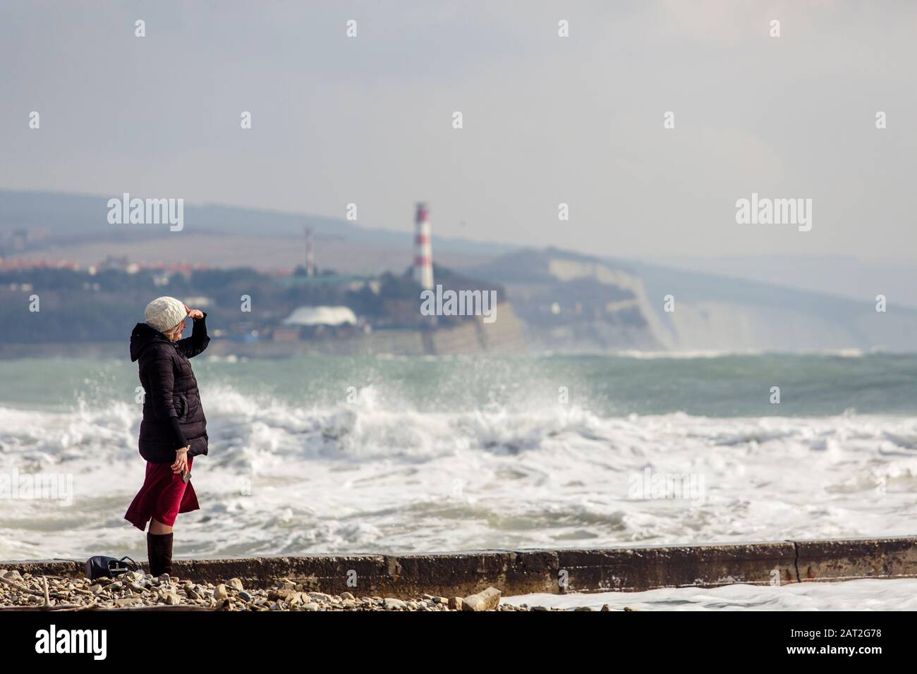 the girl looks out to sea at the raging storm waves. In the background, foam waves, lighthouse and rocks. The girl is dressed in a black jacket, white Stock Photo