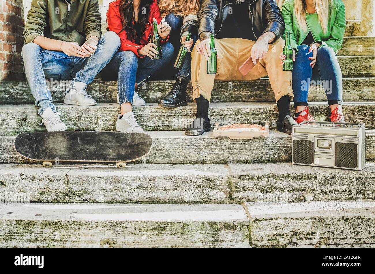 Group of friends drinking beer and eating takeout pizza outdoor -Young people sitting in staircase having fun listening music - Friendship, party, soc Stock Photo