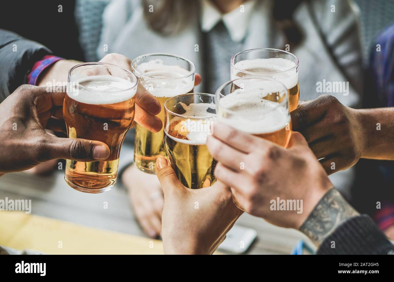 Group of friends enjoying a beer in brewery pub - Young people hands cheering at bar restaurant - Friendship and youth concept - Warm vintage filter - Stock Photo