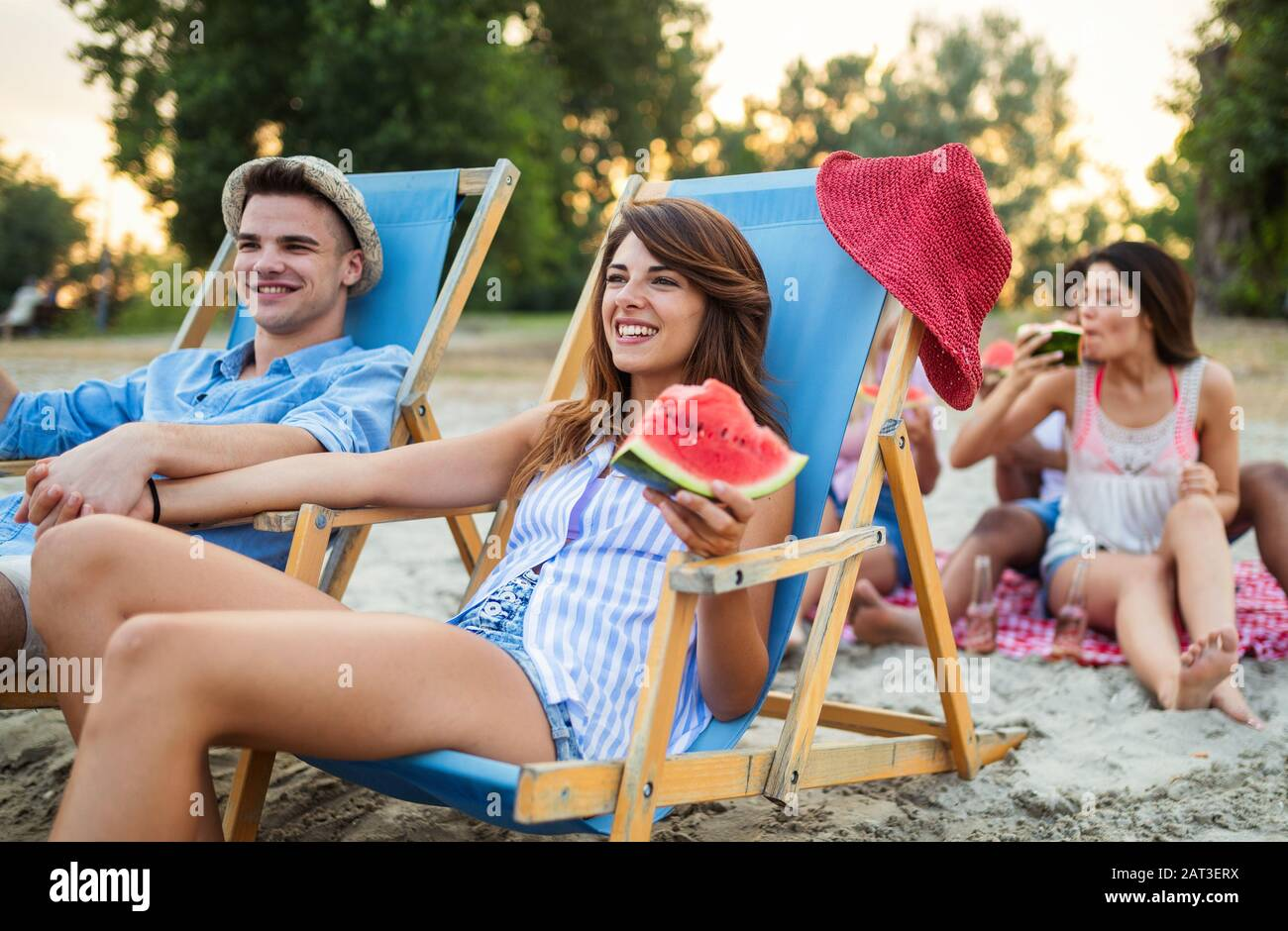 Happy friends having fun on the beach and eating watermelon. Stock Photo