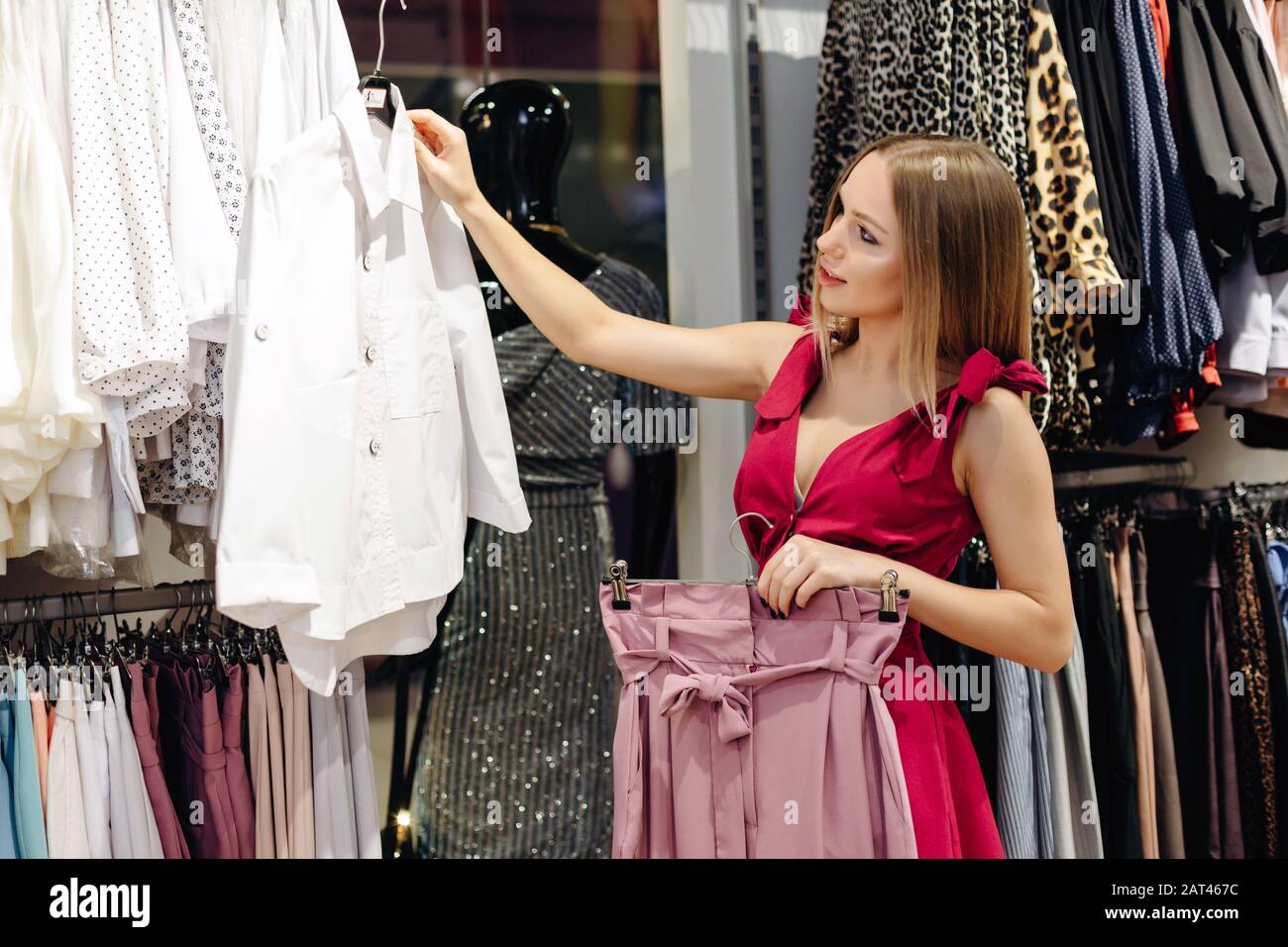 A Young Beautiful Girl In A Women S Clothing Store Chooses A White Blouse And Pink Skirt From A New Collection Stock Photo Alamy