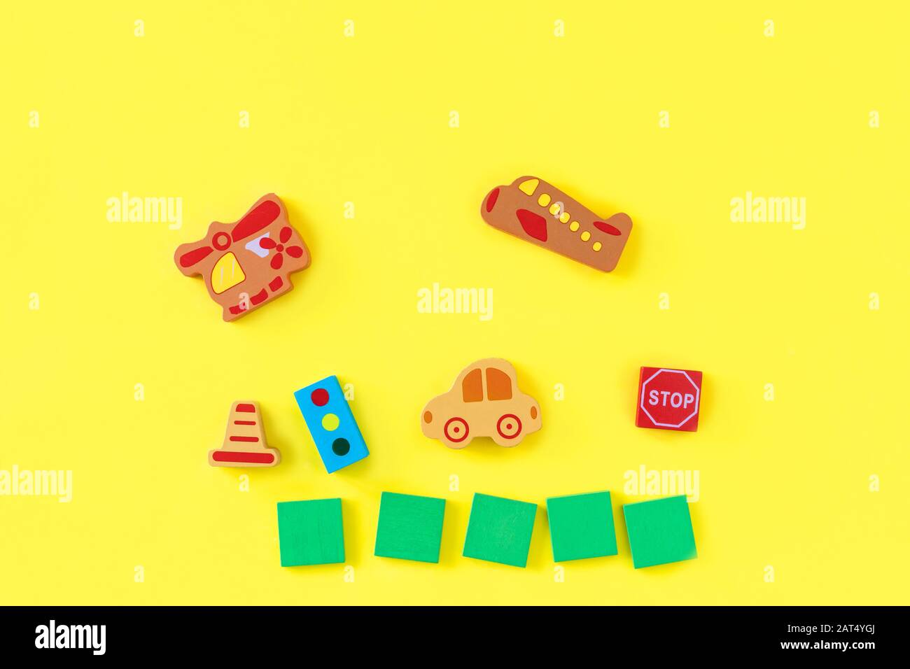 Colorful developing wooden blocks and handmade cars on yellow background. Natural, eco-friendly wooden toys for children. Top view. Flat lay. Copy space. Stock Photo