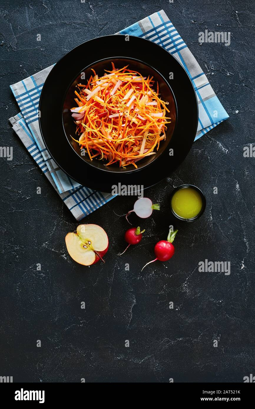 Fresh carrot radish and apple salad sprinkled with quinoa seeds and lemon zest in a black bowl on a wooden table with ingredients, vertical view Stock Photo