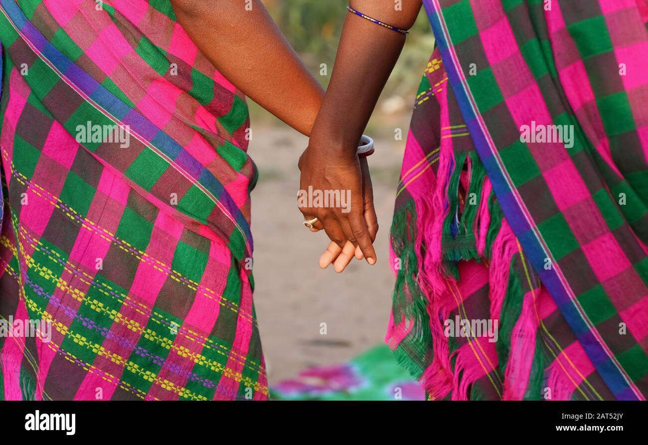 Tribal women holding hands during a traditional folk dance at Bolpur, West Bengal, India Stock Photo