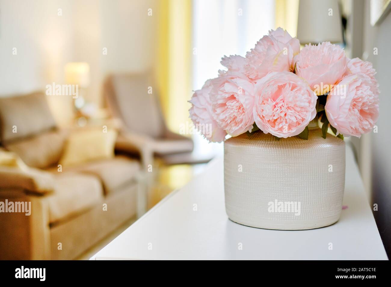 Pretty pink colour peonies flowers in white vase inside of light warm living room, selective close up focus on bouquet, no people Stock Photo