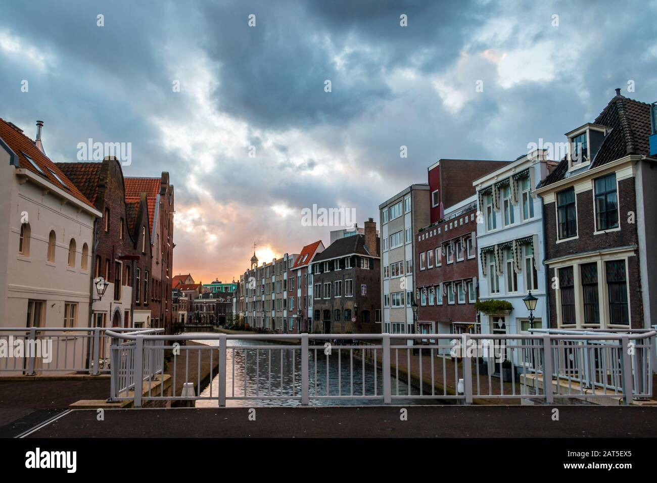 The center of Schiedam with beautiful narrow streets and small canals, photo taken in the evening hours with beautiful orange and blue clouds. Provinc Stock Photo