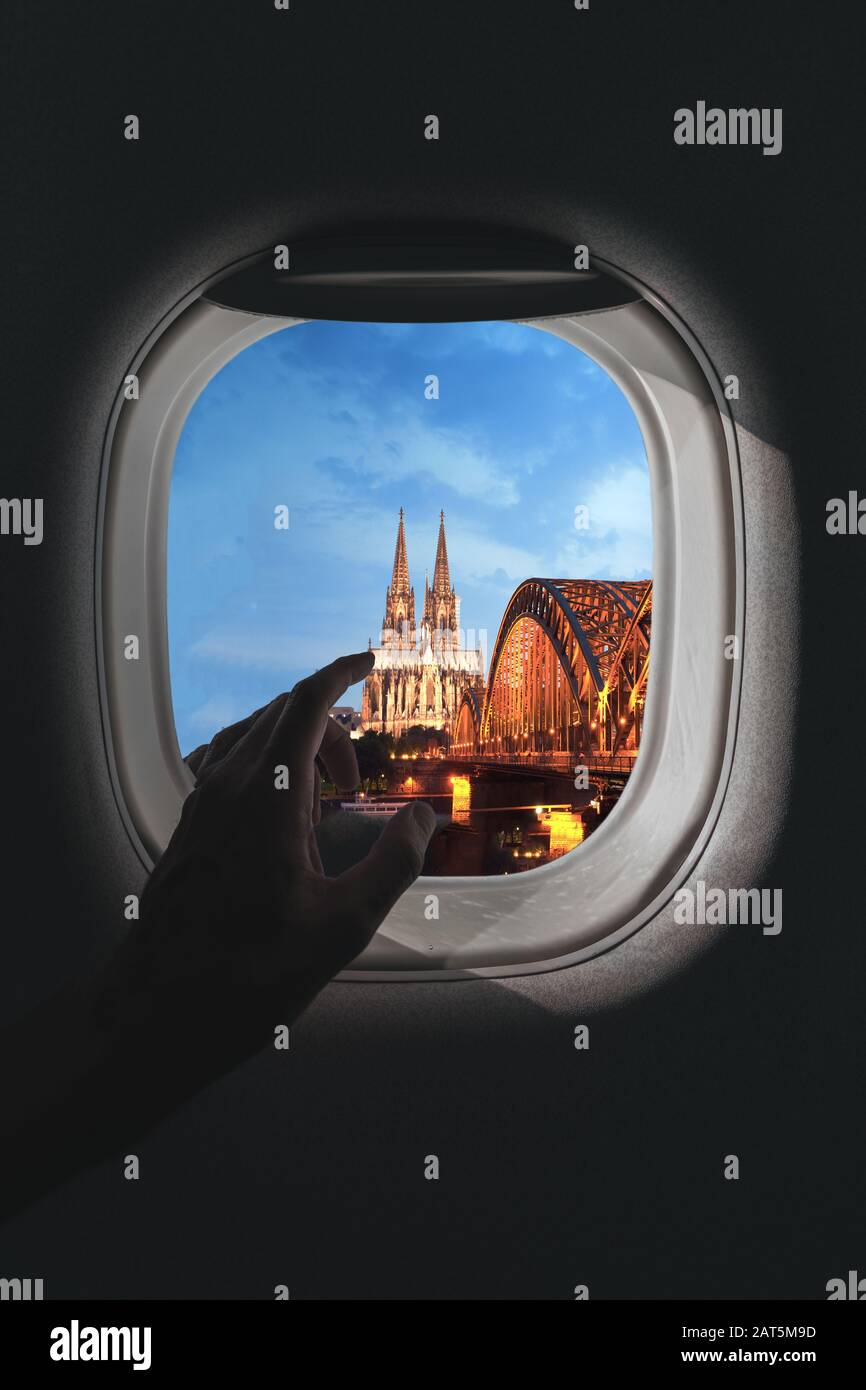 Airplane window with a aerial panorama of Cologne, Germany and Cologne Cathedral with a bridge in the evening during a flight Stock Photo