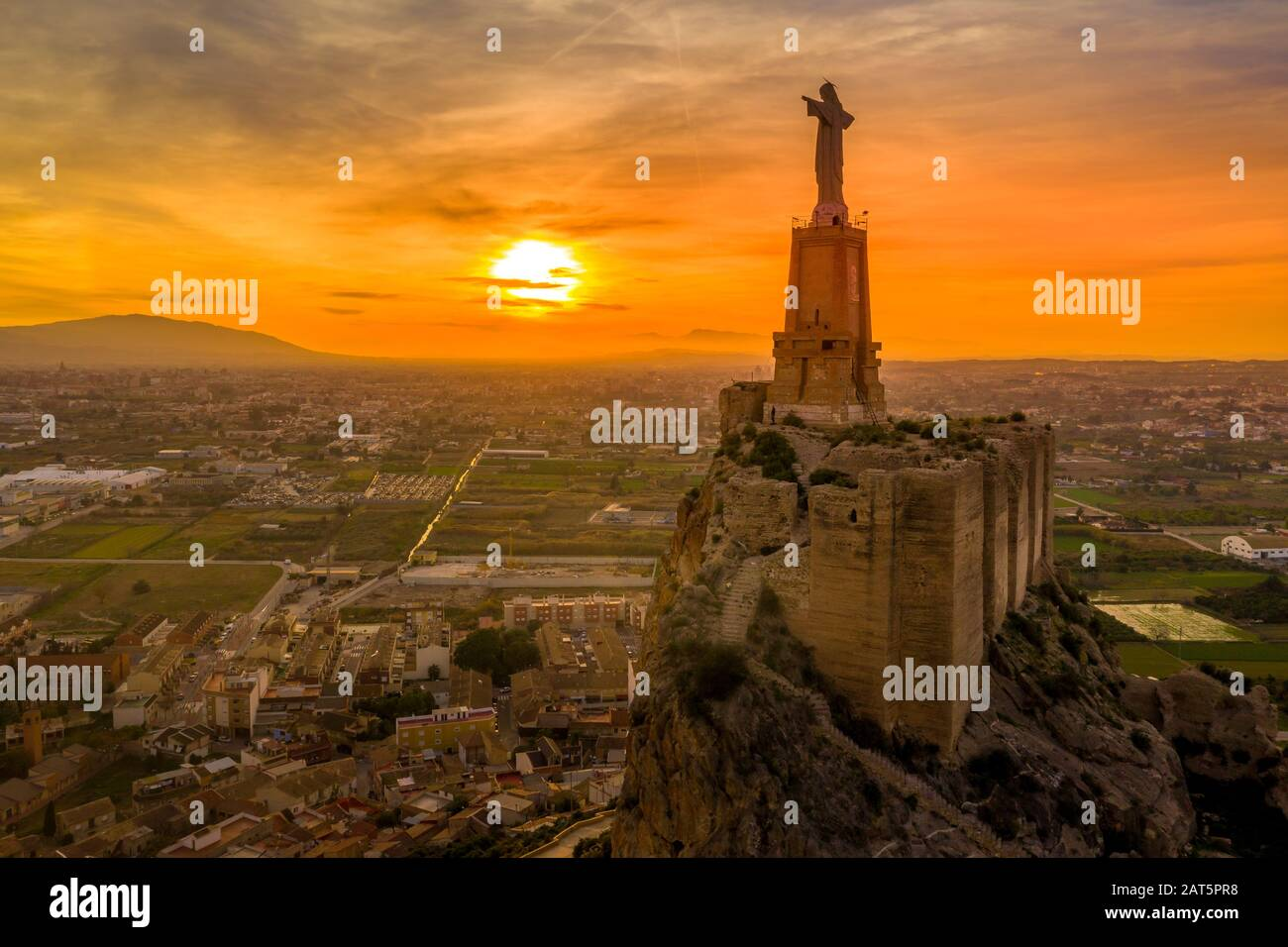Monteagudo medieval castle ruin twelve rectangular towers circling the hilltop and the sacred heart of Jesus Christ statue on top near Murcia Spain Stock Photo