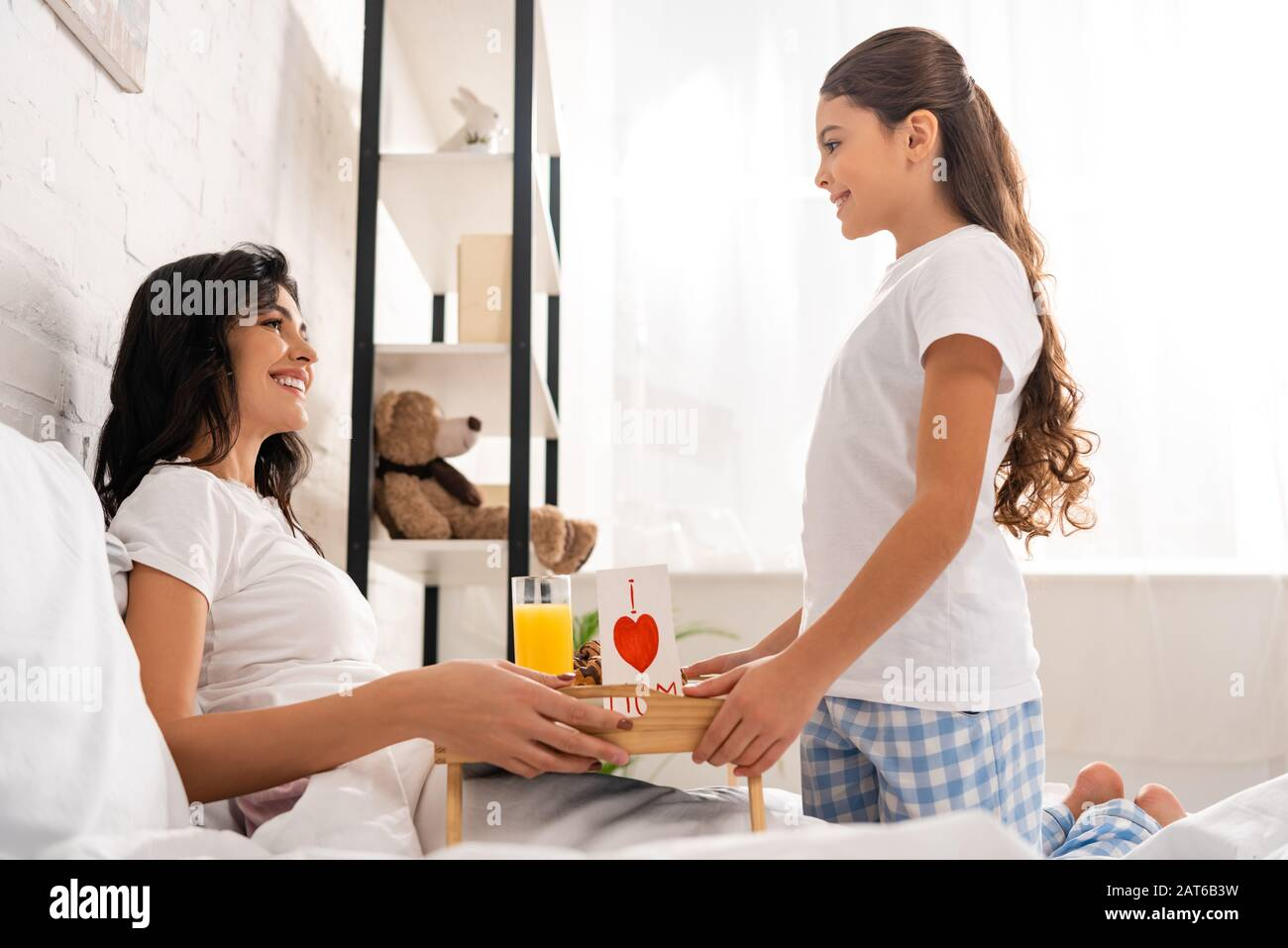 Cute Kid Giving Tray With Breakfast And Mothers Day Card With Heart Sign To Happy Mother Sitting In Bed Stock Photo Alamy