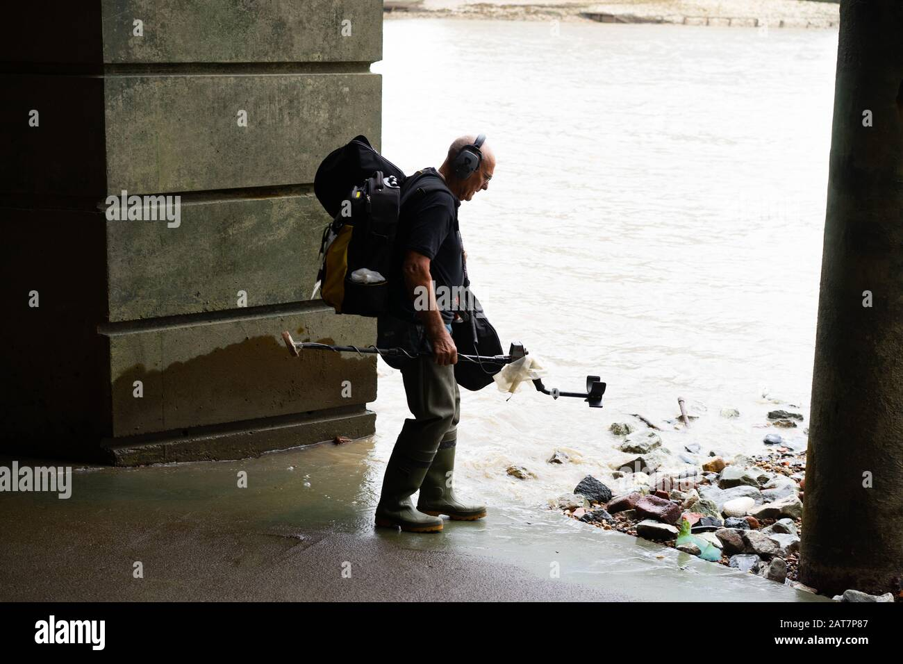 A man with metal detector works his way along the river Thames foreshore, a popular place for mudlarking and archaeological finds. Stock Photo