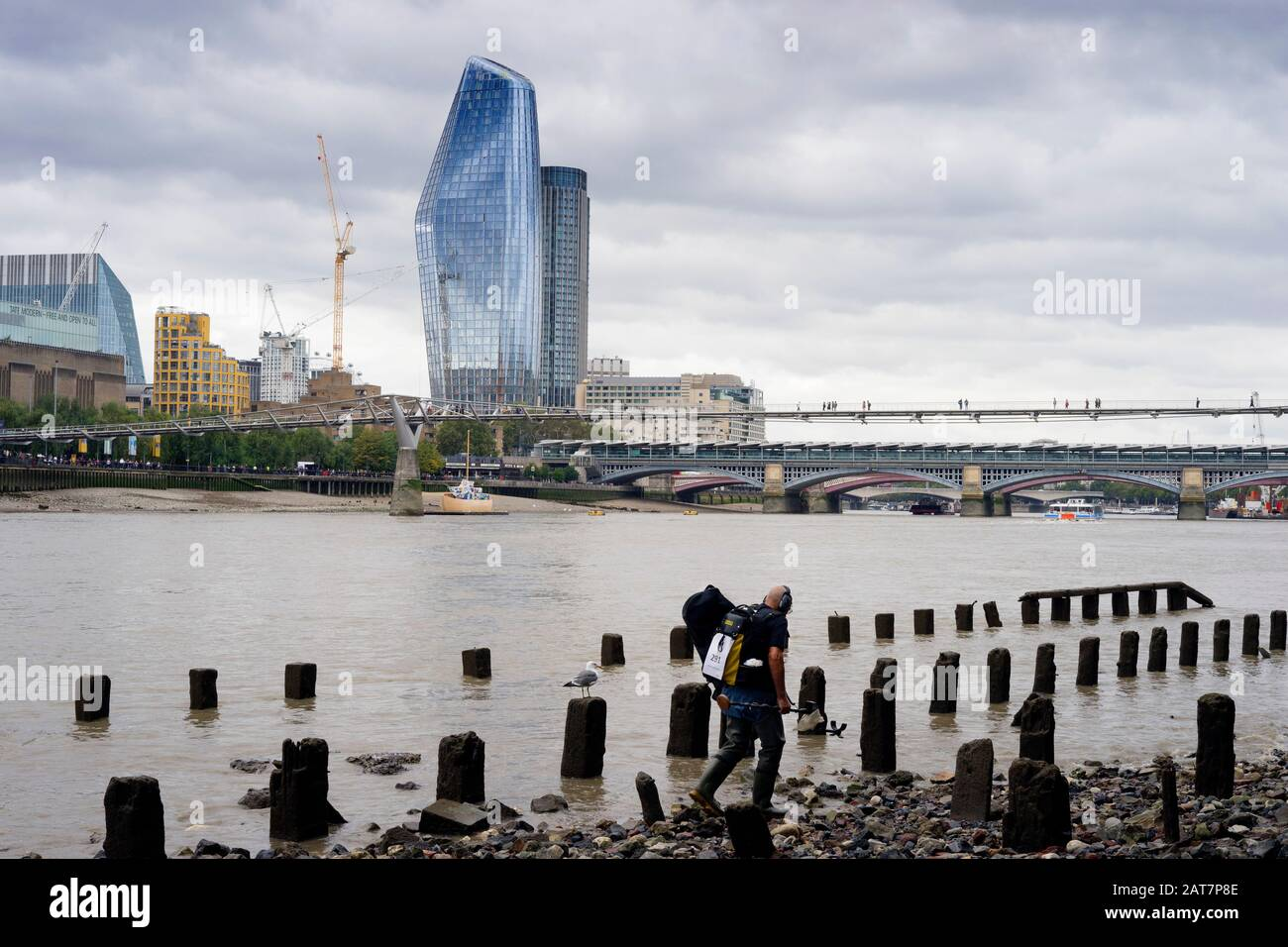 A man with a metal detector works his way along the Thames foreshore looking towards the Walkie Talkie building. With ancient posts exposed, is a popular place for mudlarking and archaeological finds. Stock Photo