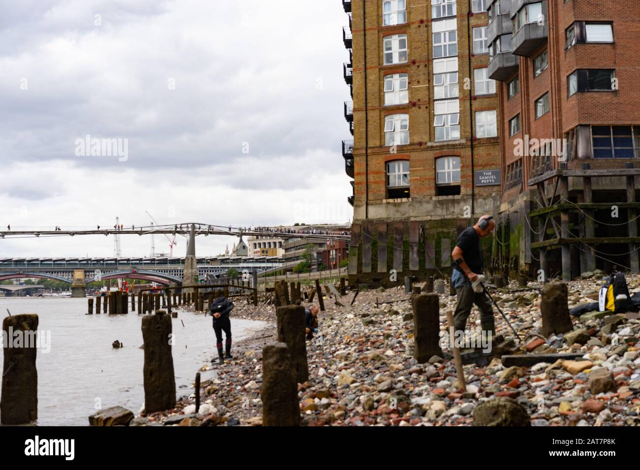 A man with metal detector works his way along the river Thames foreshore looking towards the shard building. With ancient posts exposed, is a popular place for mudlarking and archaeological finds. Stock Photo