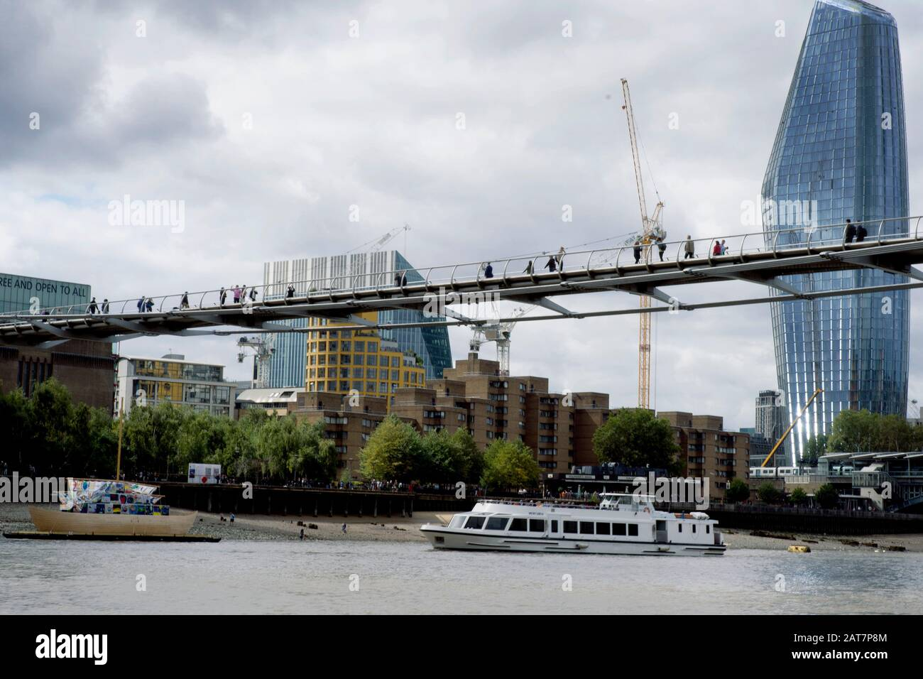 A view of  the river Thames foreshore, with the Walkie Talkie building in the background, as a tourist cruise boat passes under the Millennium bridge. The Thames is a popular place for mudlarking and archaeological finds. Stock Photo